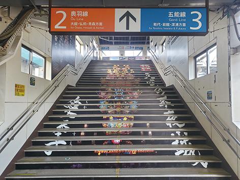 〈能代市〉JR東能代駅天空の不夜城ラッピング▷駅のホーム階段に名物の巨大灯籠